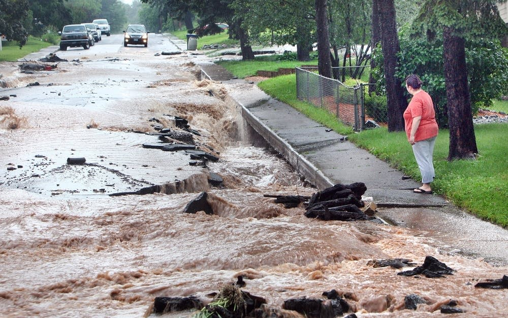 Water flows down a damaged street