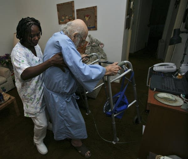 A nurse's aide helps an elderly patient
