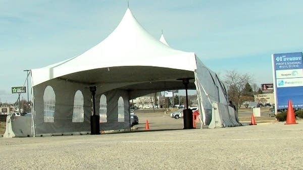 A large white tent in a parking lot.