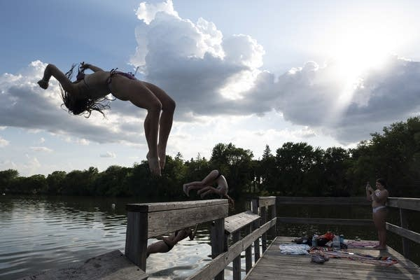 A group of girls do back flips into a lake.