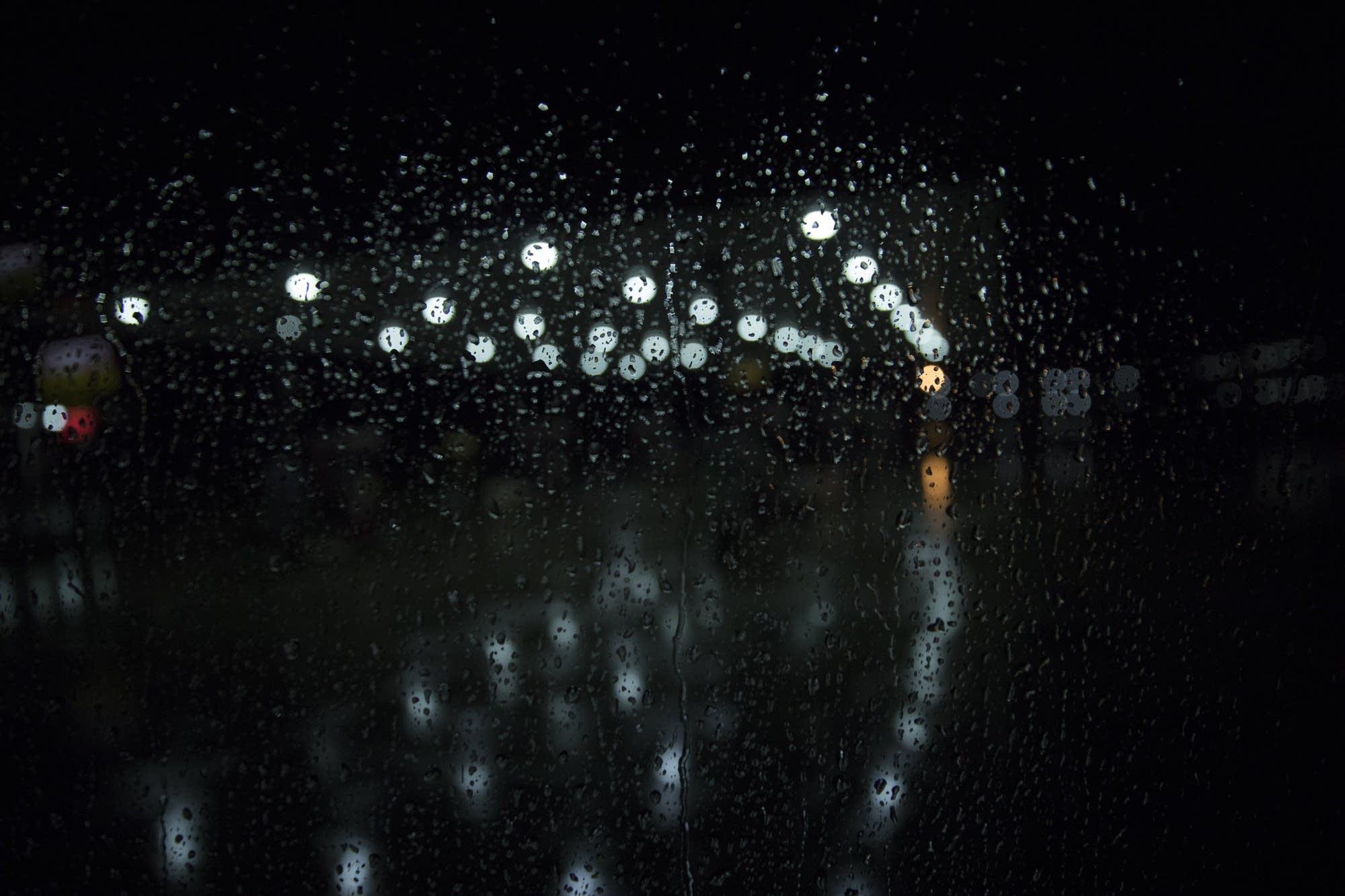 Rain drips down the window of the charter bus.