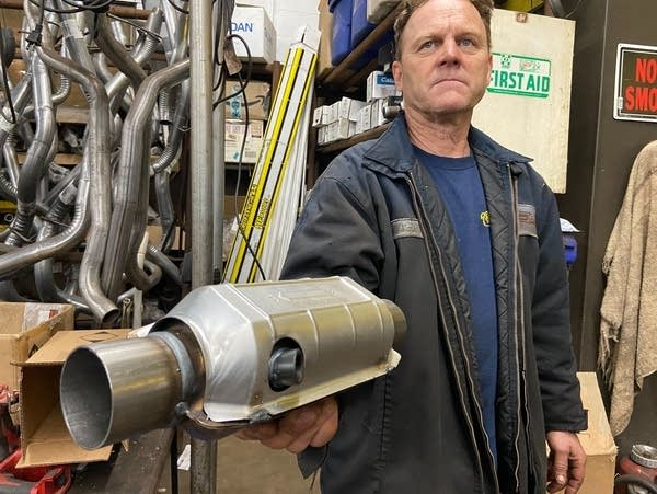 A man holds a replacement catalytic converter.