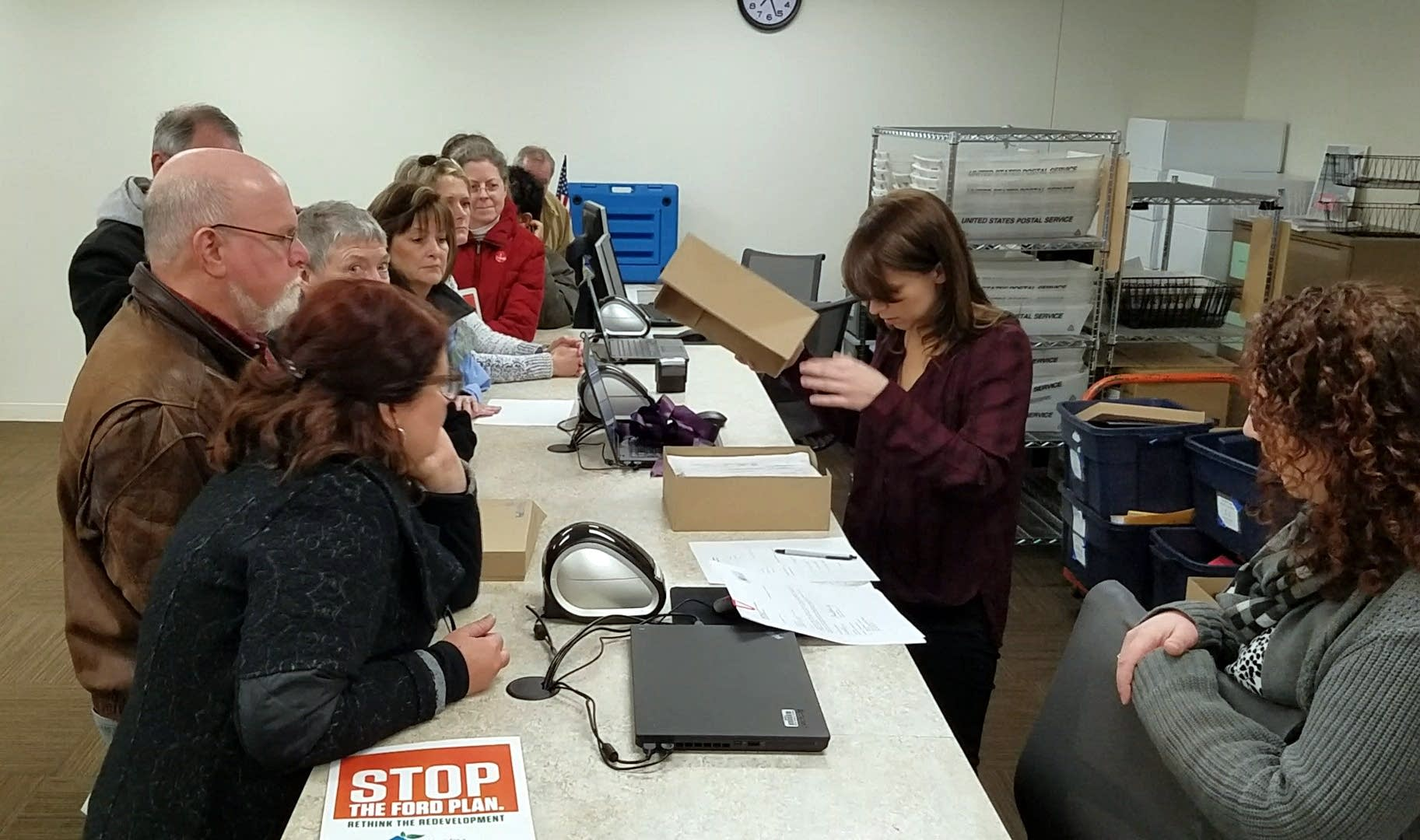 Elections specialist Kristine Grill looks over a box of petitions.