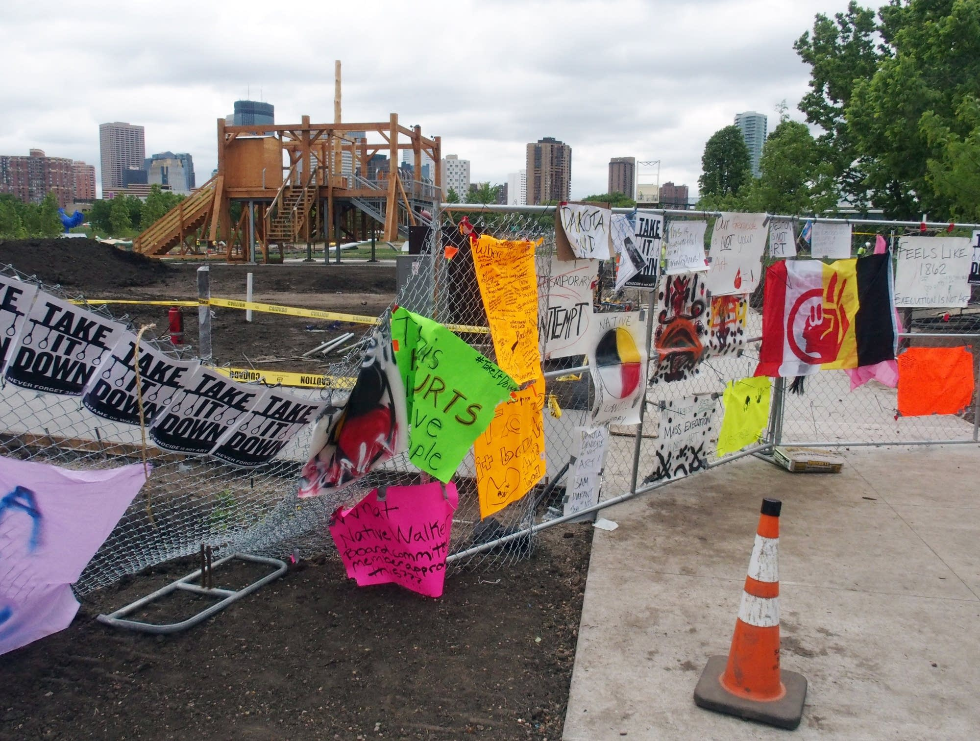 The sculpture stands behind a fence covered with banners and posters.