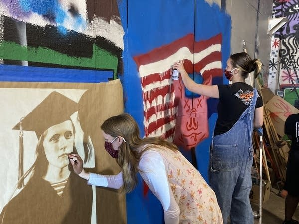 Two students work on a mural.