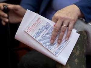 A US Senator holds a pocket US Constitution