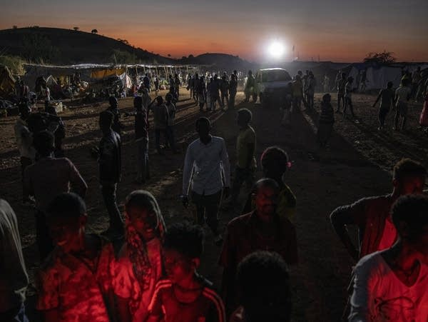 People gather near their shelters in a refugee camp