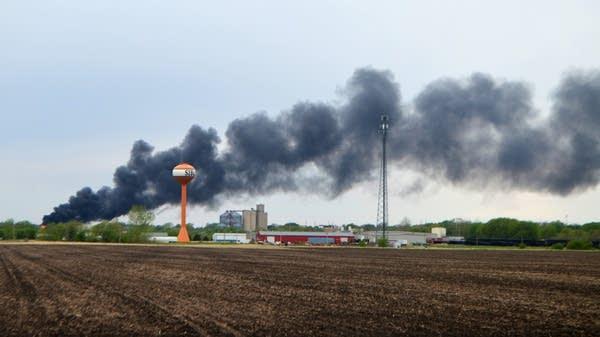 Smoke billows from derailed train cars