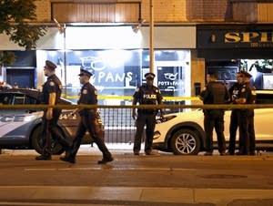 Police officers walk the scene of a shooting in Toronto.