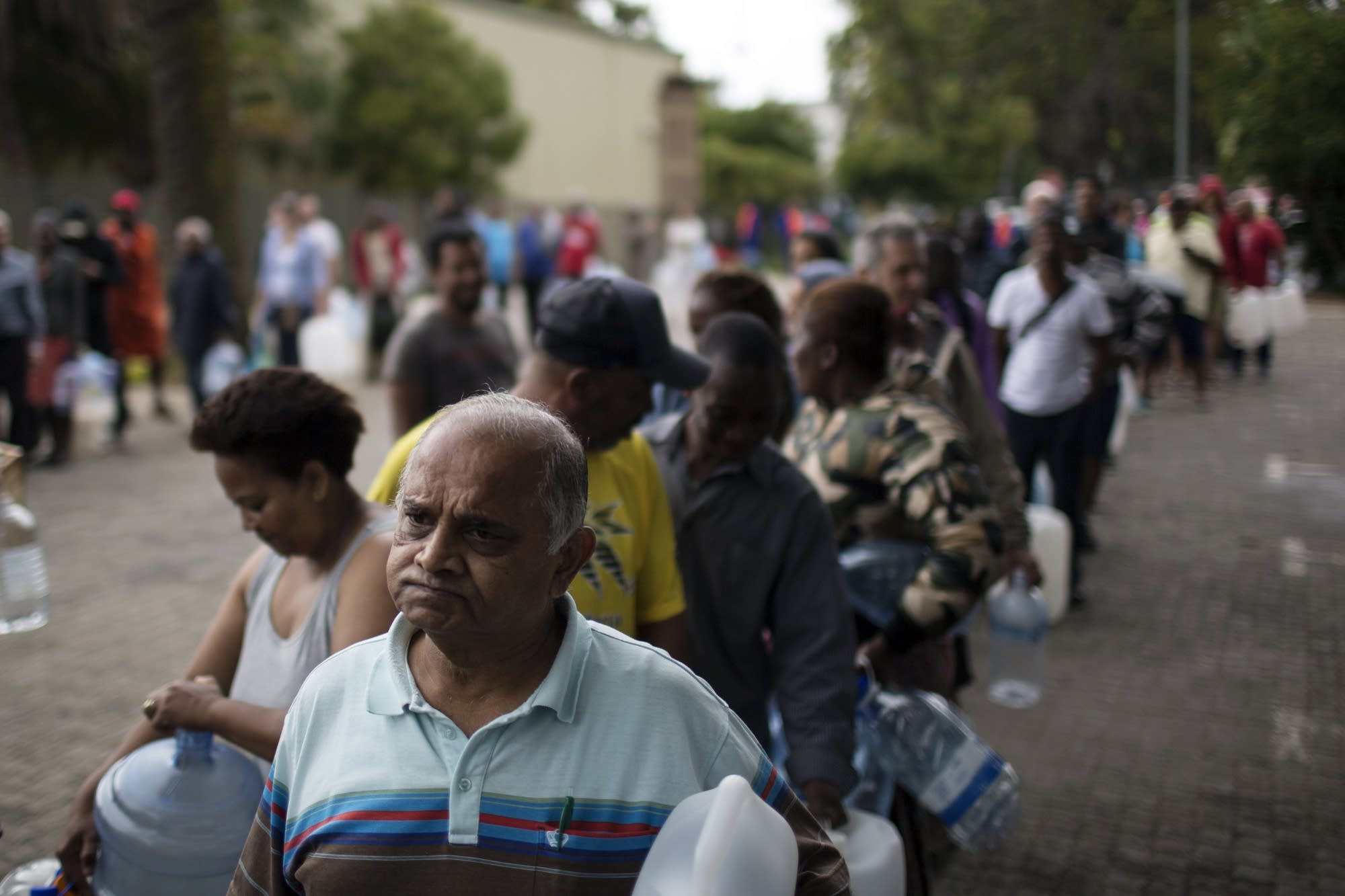 Cape Town residents queue to fill containers with water amid a drought