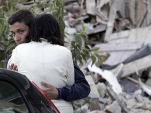 Two people hug after the earthquake in Italy