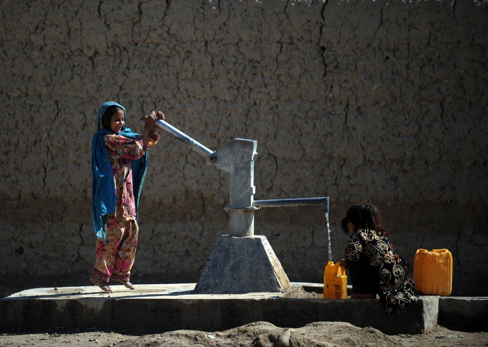 Afghan children pump water from a well