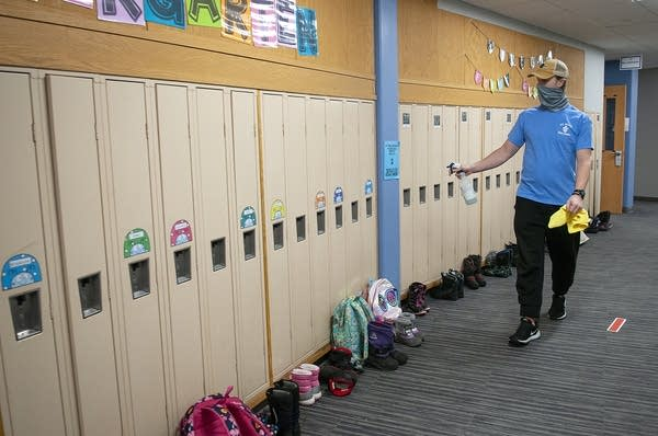 A man uses a plastic bottle to spray lockers with sanitizer.