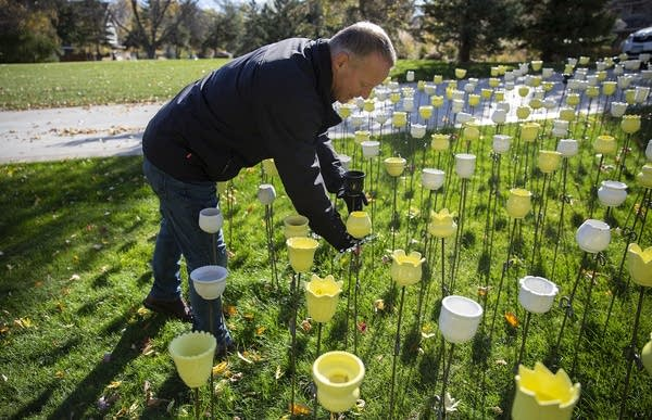 A man leans over a display of white, yellow and black ceramic flowers.