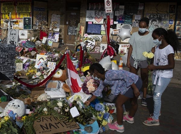 Three youth put flowers at a memorial.