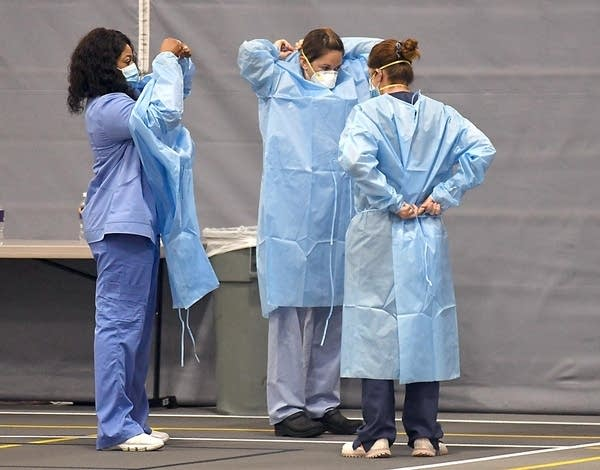 Three nurses put on personal protective equipment.