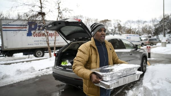 A man brings pans of food out of the trunk of a vehicle.