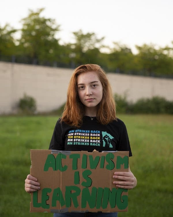 A teenage girl holds a sign that reads activism is learning