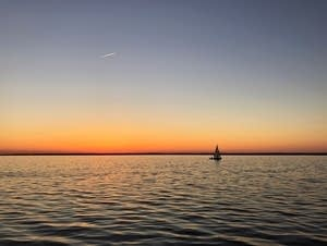 A lone sailboat floats on a calm sea.