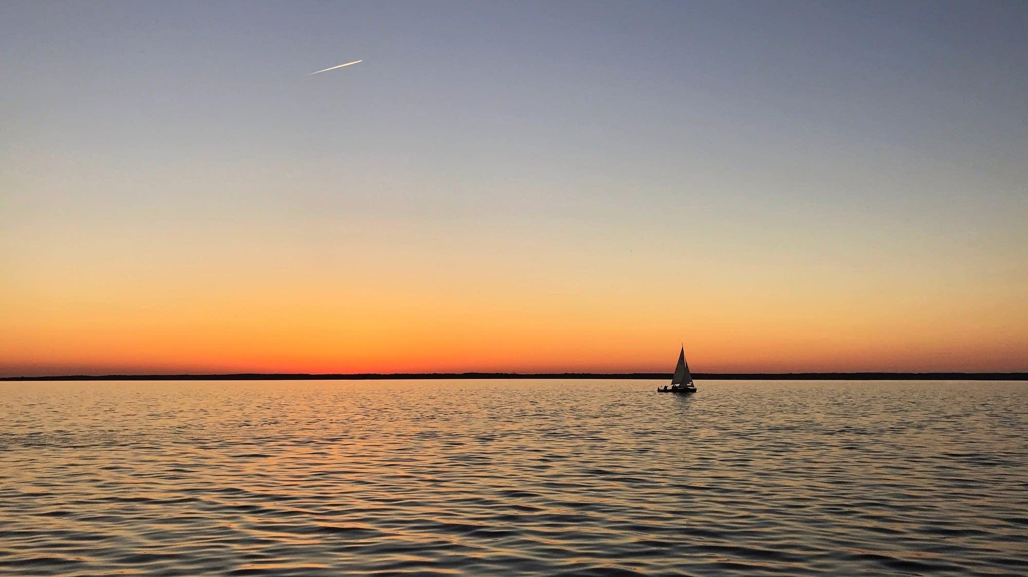 A lone sailboat floats on a calm sea.