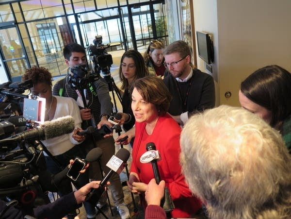 Amy Klobuchar talks in front of press microphones