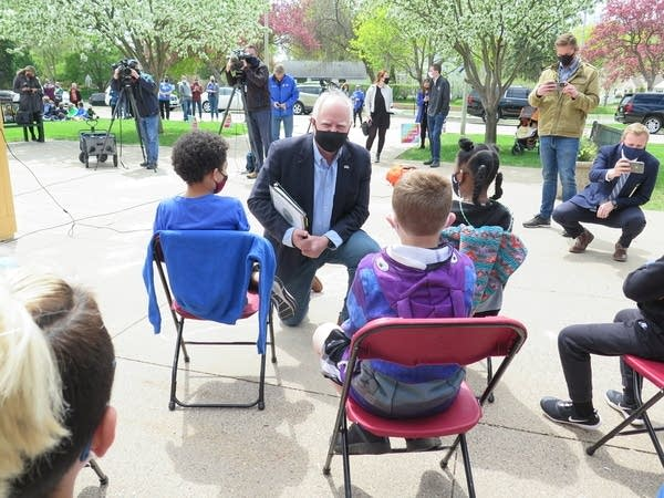 The governor kneels down to talk to a few students outside.