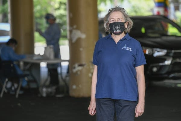 A woman in a mask stands in a parking lot.