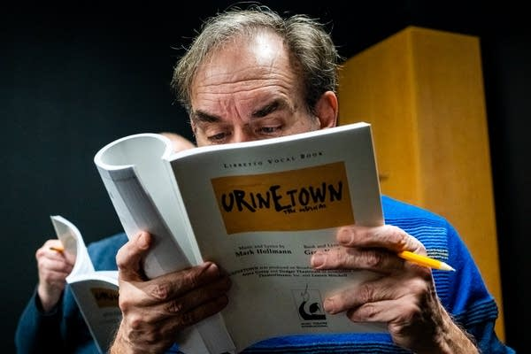 A man holds a script near his face and reads.