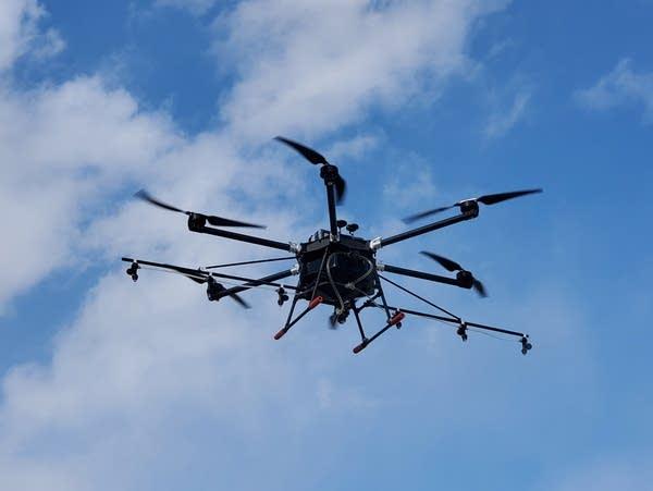 a small drone flies against a blue sky