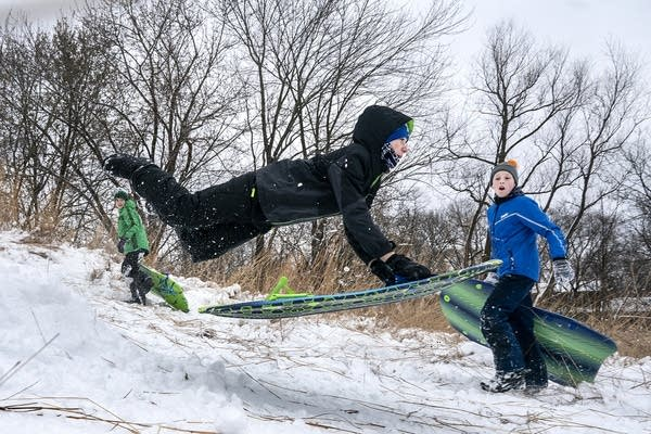 A teen flies in the air with a sled