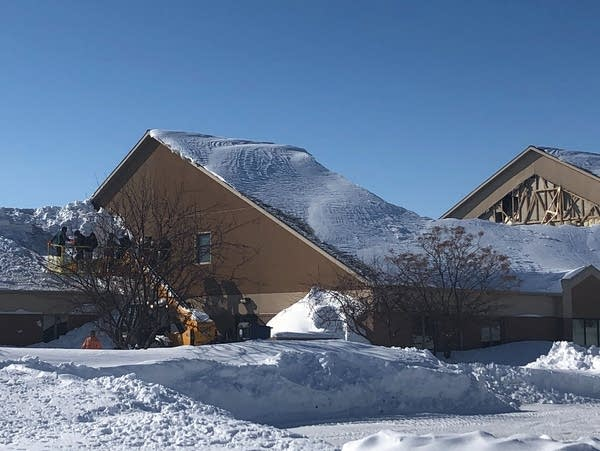 Crews work to clear snow off St. Francis de Sales Church in Moorhead