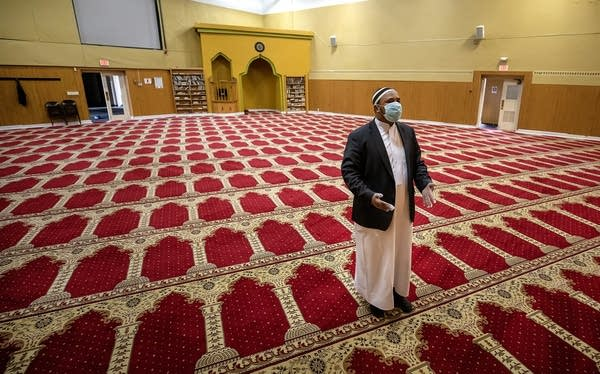 A man stands in an empty mosque.