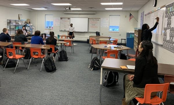 Two students lead a discussion in a classroom.