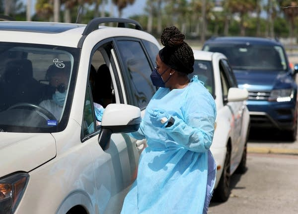 A health care worker stands outside a car at a drive-thru vaccine site.