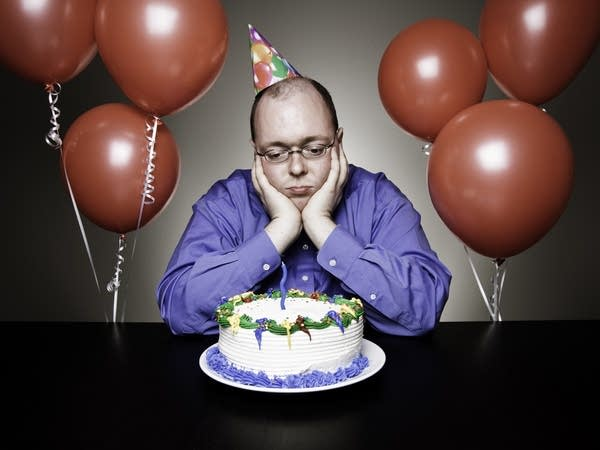 Lonely middle aged white man looking sadly down at birthday cake
