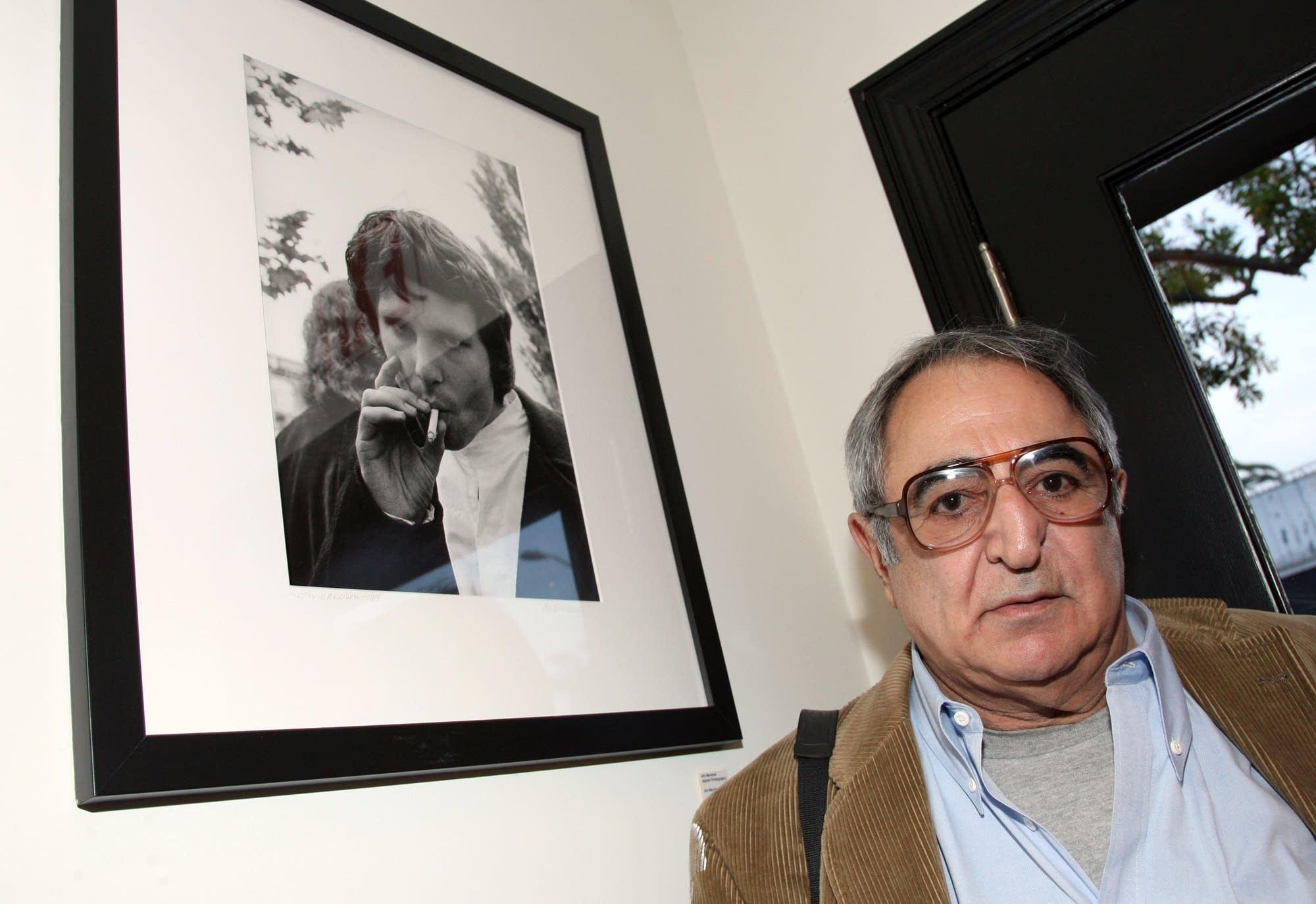 Photographer Jim Marshall poses with his photo 'Jim Morrison Smoking'