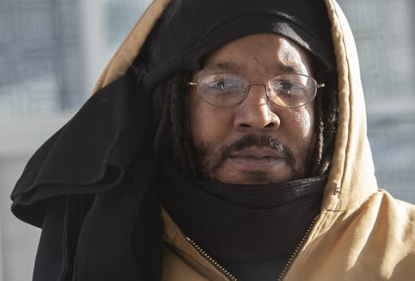 Dandre Pernell ties three thermal knit shirts around his head to keep warm
