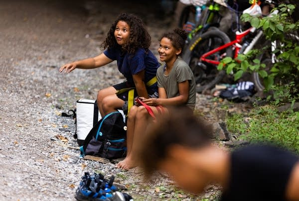 Two girls sit and watch a friend rock climb.