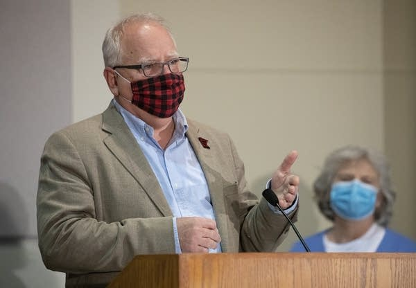 A man wearing a red and black plaid face mask gestures at a podium.