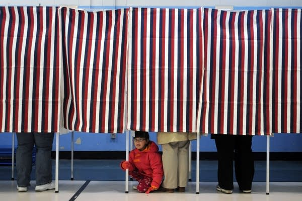 A young girl looks out from a voting booth.