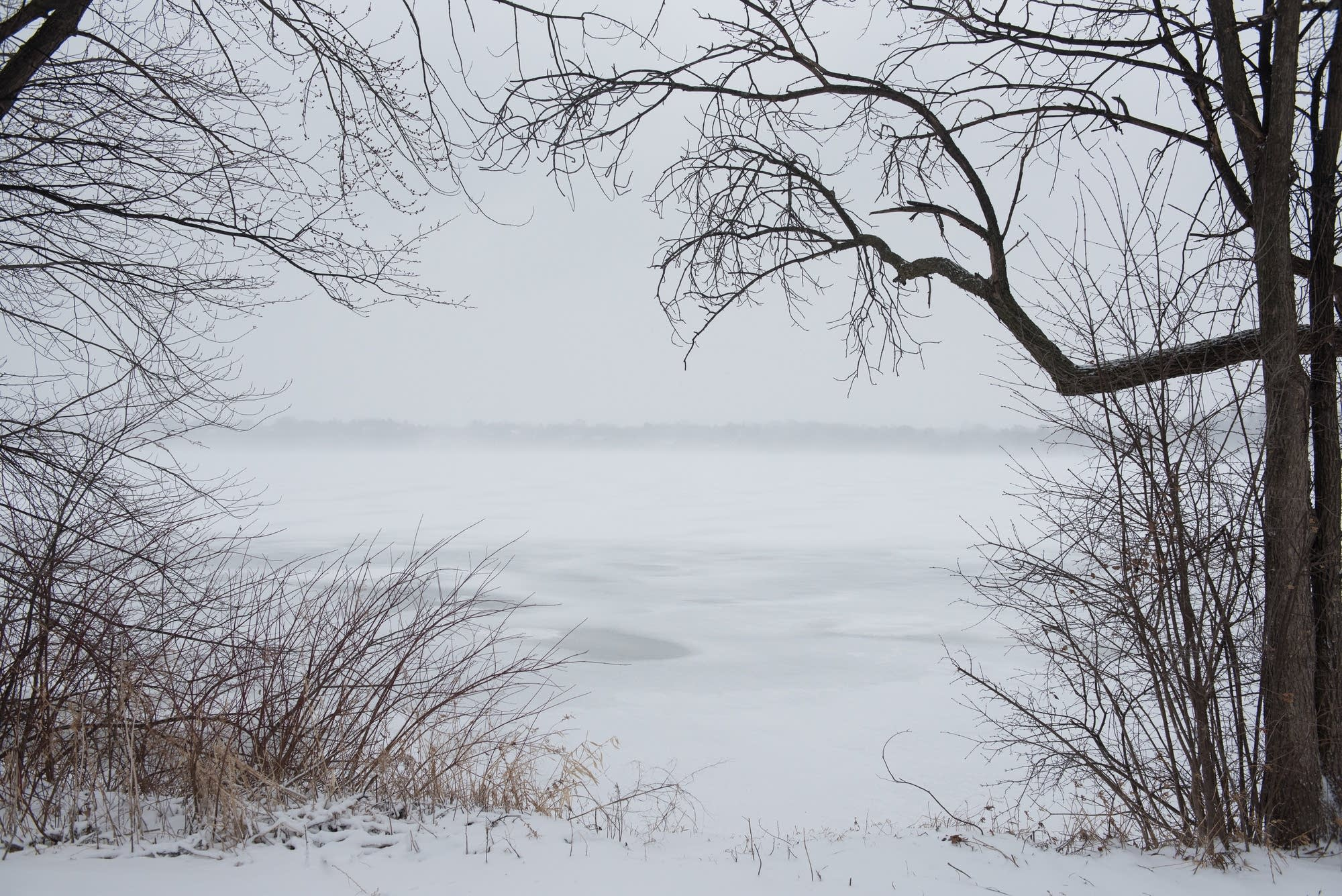 Snow blows across the icy surface of Lake Harriet Saturday morning.