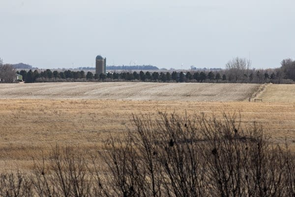 Wind turbines are seem beyond a farm in the distance.