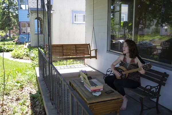 A woman playing an instrument on her front porch.