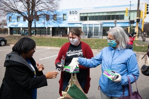 Women hand out masks and gloves in a parking lot.