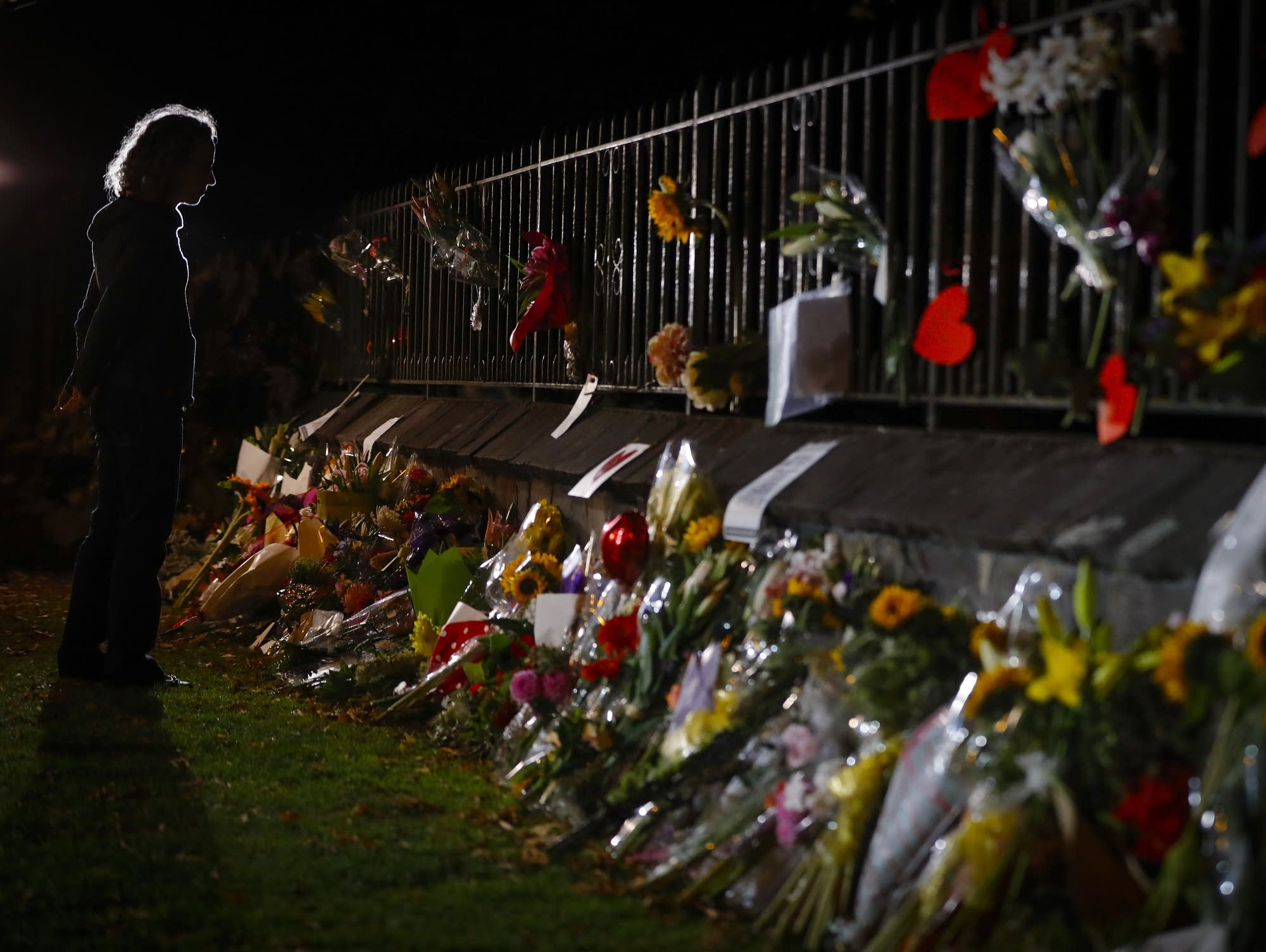 Mourners pay their respects at a makeshift memorial