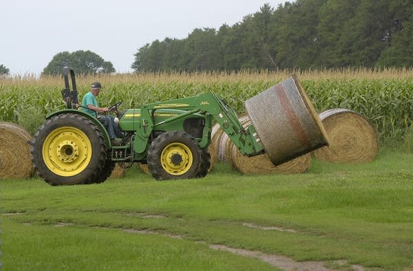 A man uses a farm machine to move a bale of hay.