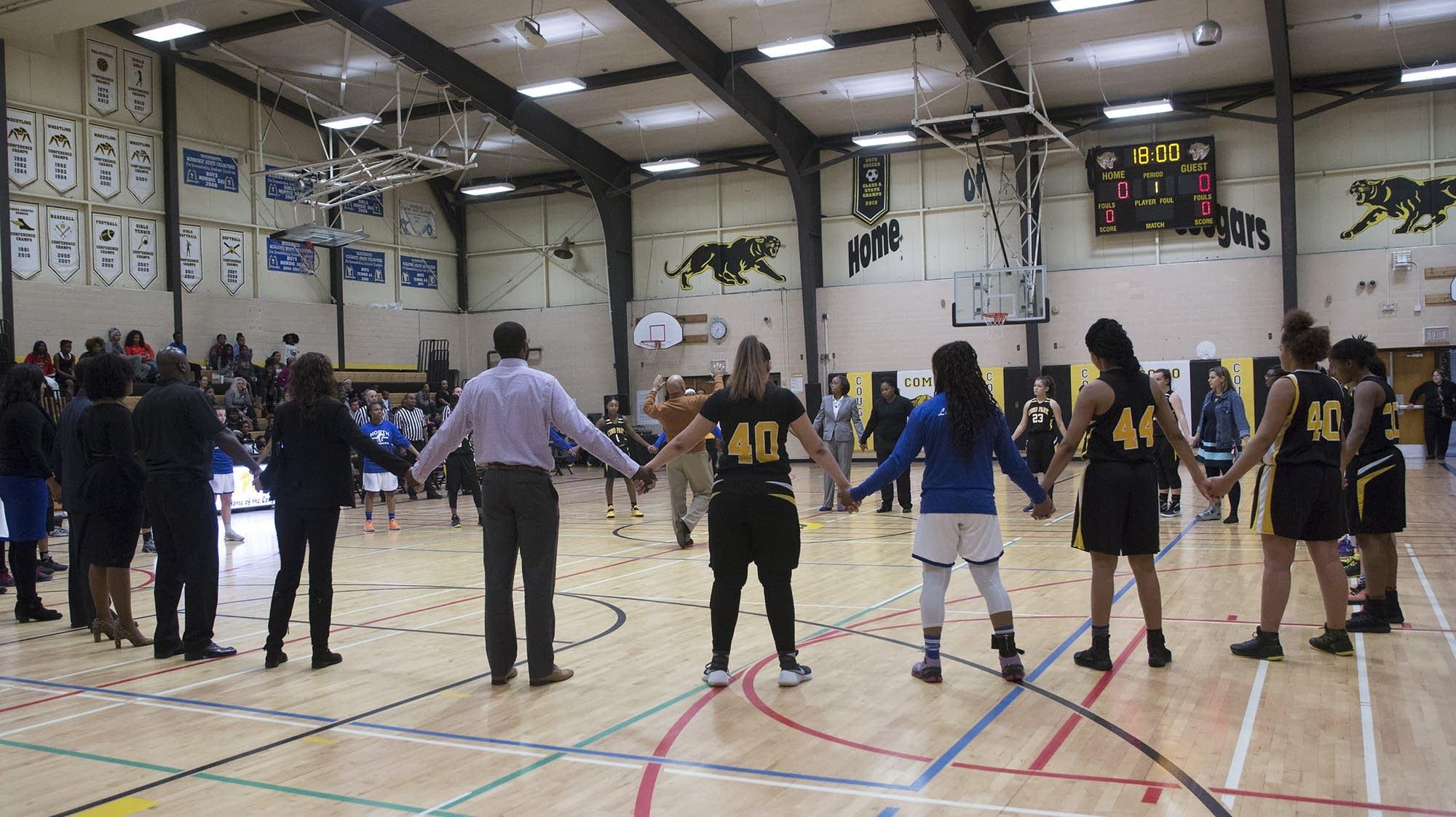 Como and North High basketball teams join hands.