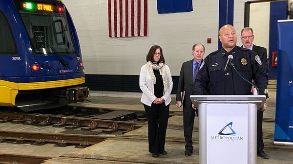 An officer for Metro Transit stand behind a white podium.
