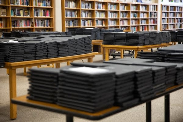 Hundreds of laptops sit on tables.