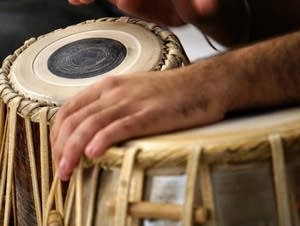 A sleepy tabla player rests his hand on the drumhead